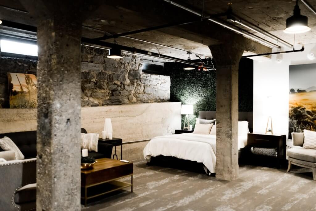 Bedroom in basement with exposed walls