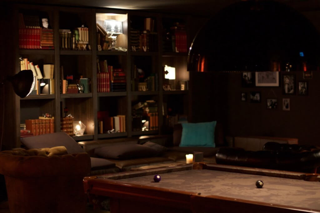 Under garden basement entertainment room with pool table and bookshelves