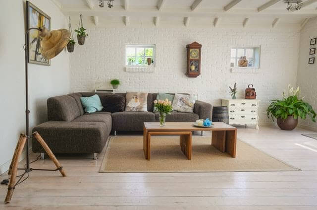 Underground living room with small windows, grey sectional sofa, brown wooden table